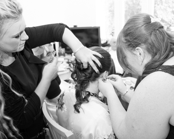 Bridesmaid and hairdressser attending to the bride on the morning of the wedding