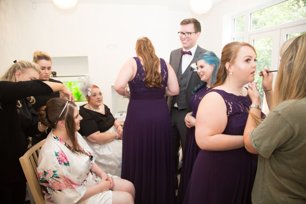 All the bridesmaids with the bride makeup artist and hairdresser in the living room getting ready on the morning of the wedding