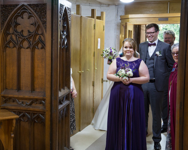 Bridesmaid walking down the aisle in floor length purple dress