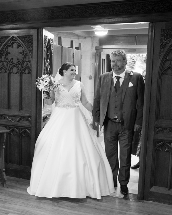 Bride and godfather walking down the aisle at Bolsover Parish Church