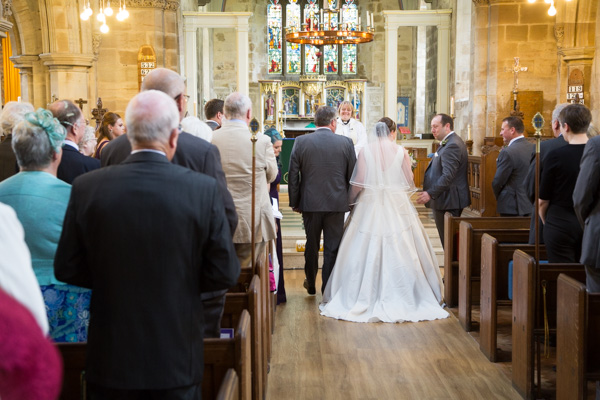 Groom turning to see the bride as she walks down the aisle at Bolsover Parish Church