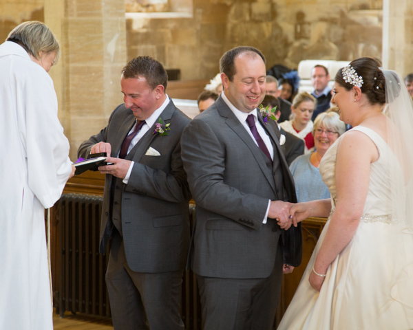 Bride and Groom holding hands during the exchanging of the rings