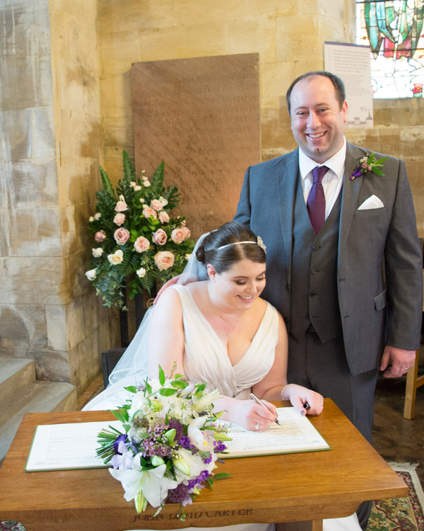 Bride signing the register with the groom standing behind her looking at the camera and smiling