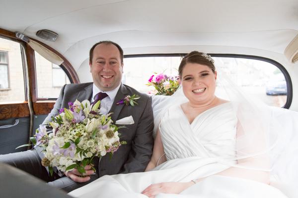 Groom with bride inside the wedding car