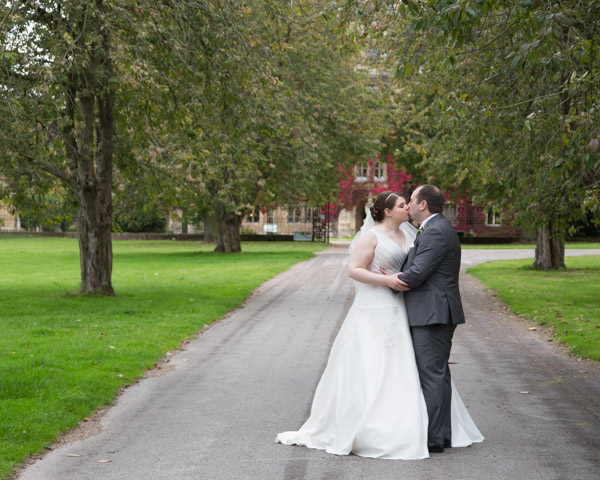 Bride and Groom kissing in between trees at Thoresby Hall Wedding