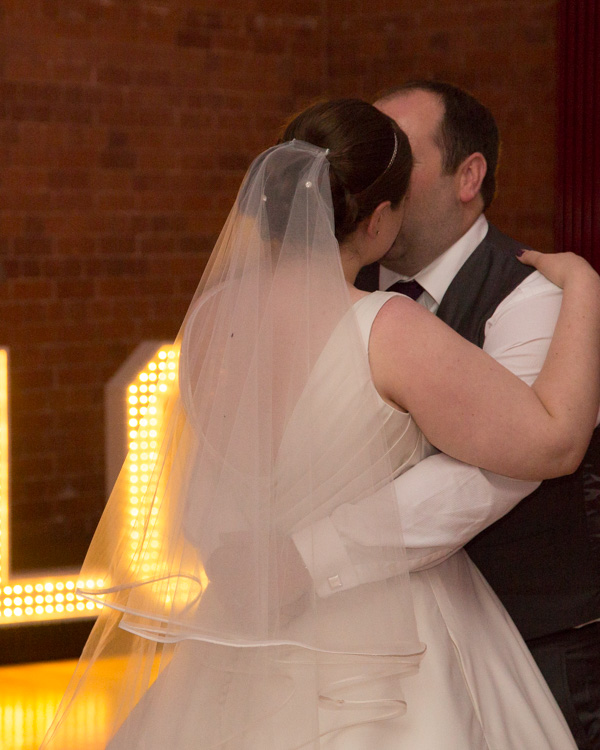 Bride and groom dancing during their first dance with love light up letters in the background