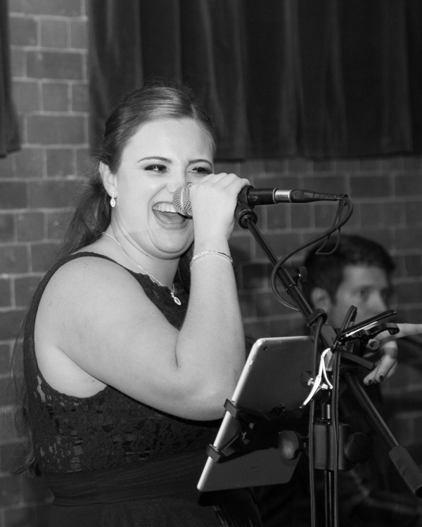 Bridesmaid singing with live band during the wedding reception at Thoresby Courtyard