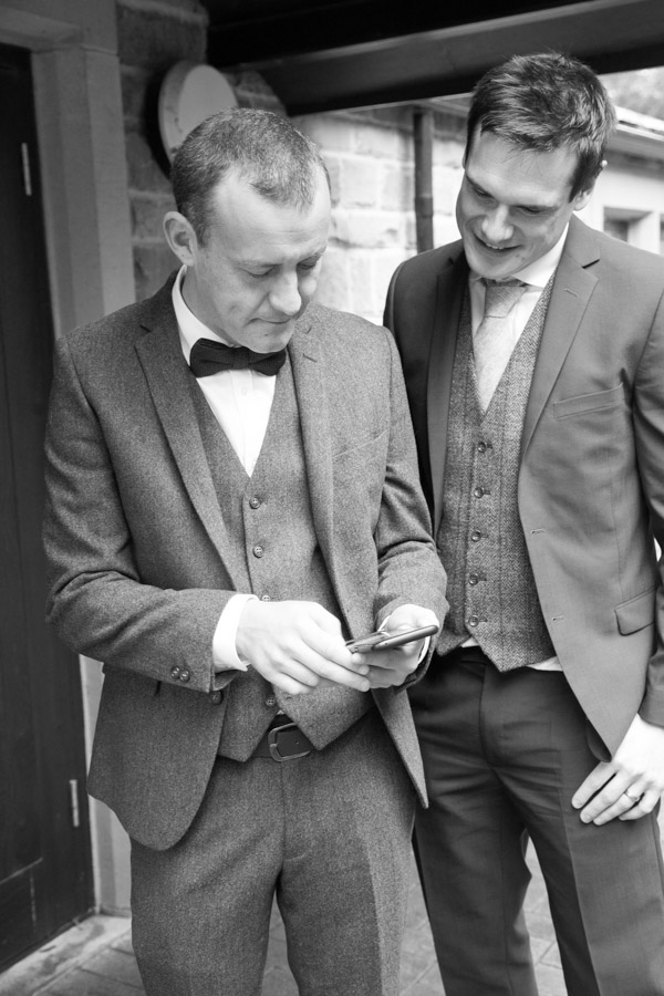 Groom and best man looking at a phone outside the wedding venue at bradfield village hall