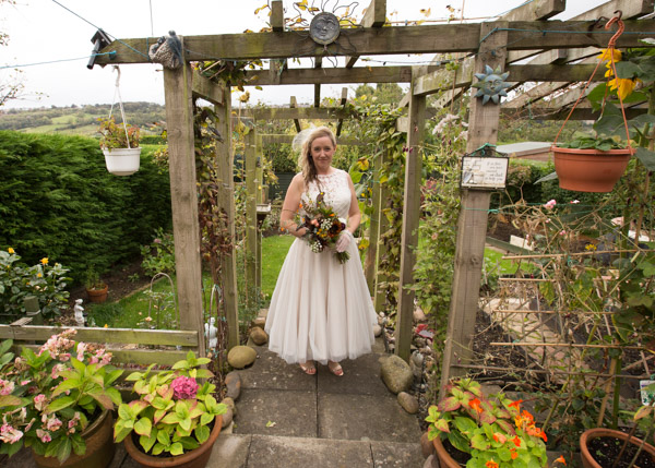 Bride with her bouquet in her back garden before the wedding ceremony