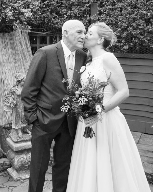 Bride and Father of the bride kissing in the garden on the morning of the wedding