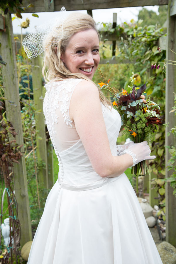 Bride looking over her shoulder holding her bouquet on the morning of the wedding