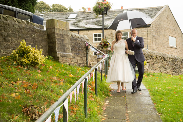 Father of the bride holding an umbrella to walk into the ceremony with