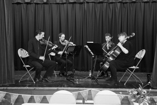 String quartet playing as guests arrived into the wedding ceremony room at Bradfield Village Hall
