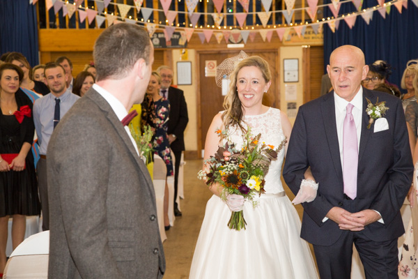 Bride walking down the aisle with her father and smiling at the groom