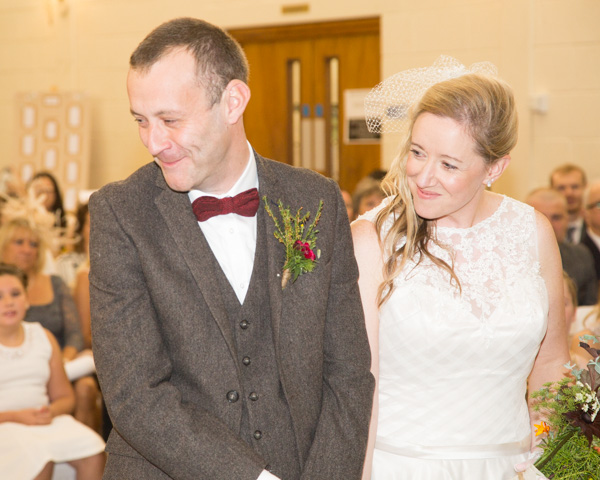 Bride and groom smiling at a guest during the wedding ceremony at Bradfield Viallge Hall