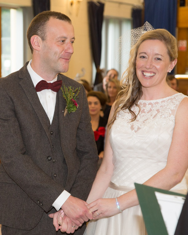 Bride and Groom smiling and holding hands at Bradfield Village Hall wedding