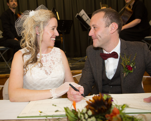 Bride and Groom signing the register with string quartet playing in the background