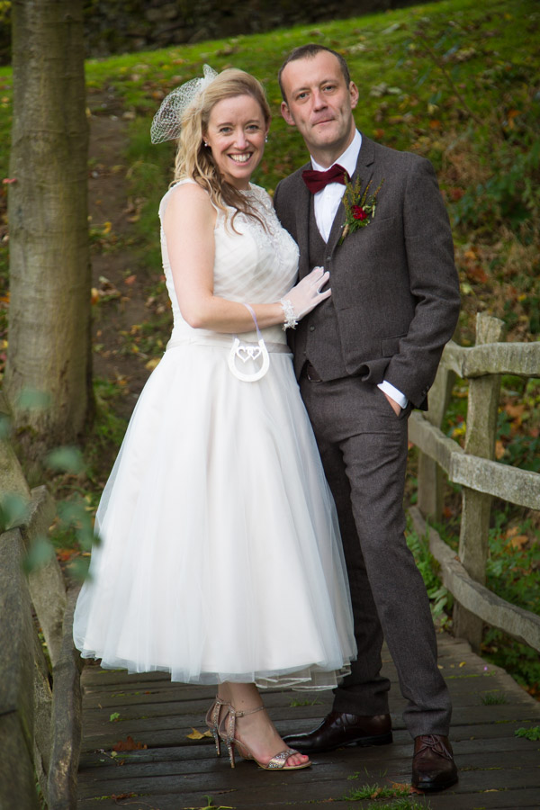 Bride and groom on the bridge in the grounds of Bradfield Village Hall