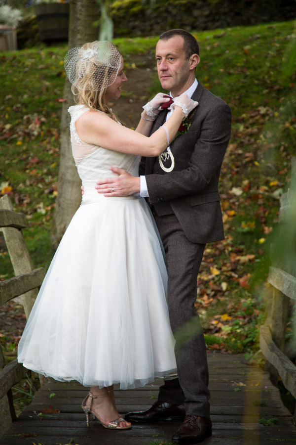 Bride fixing Grooms bow tie on the bridge at Bradfield Village Hall
