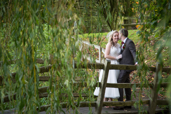 Bride and groom talking on the bridge at Bradfield Village Hall