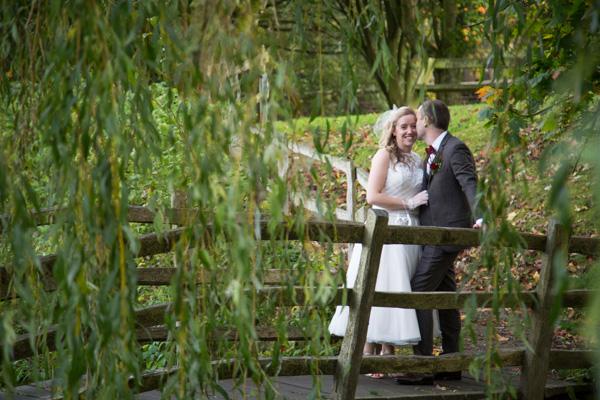 Bride and groom talking on the bridge at Bradfield Village Hall