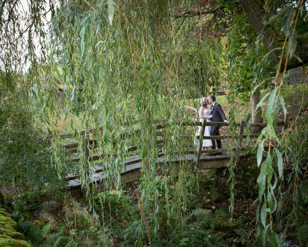 Groom with bride on the bridge at Bradfield Village Hall