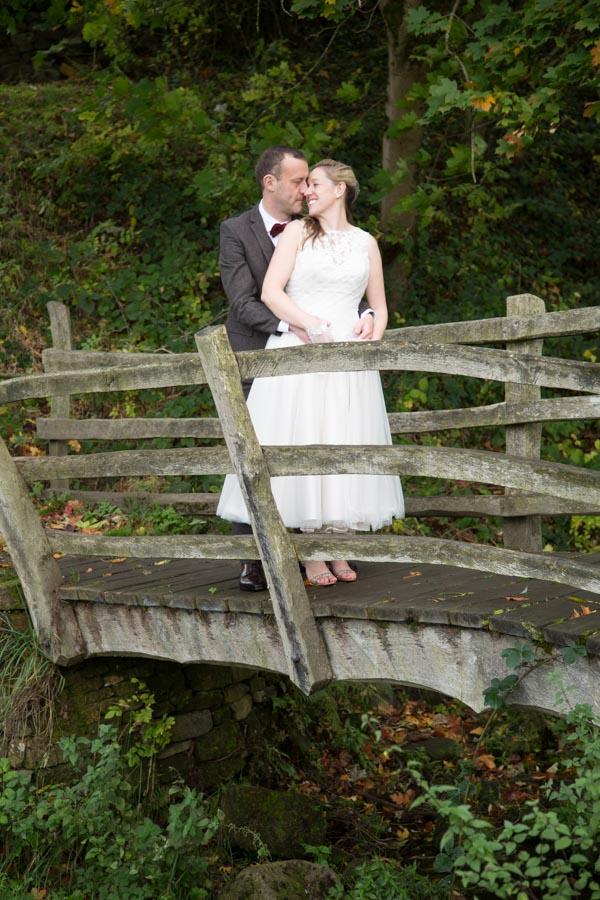 Bride and Groom cuddling on the bridge at Bradfield Village Hall