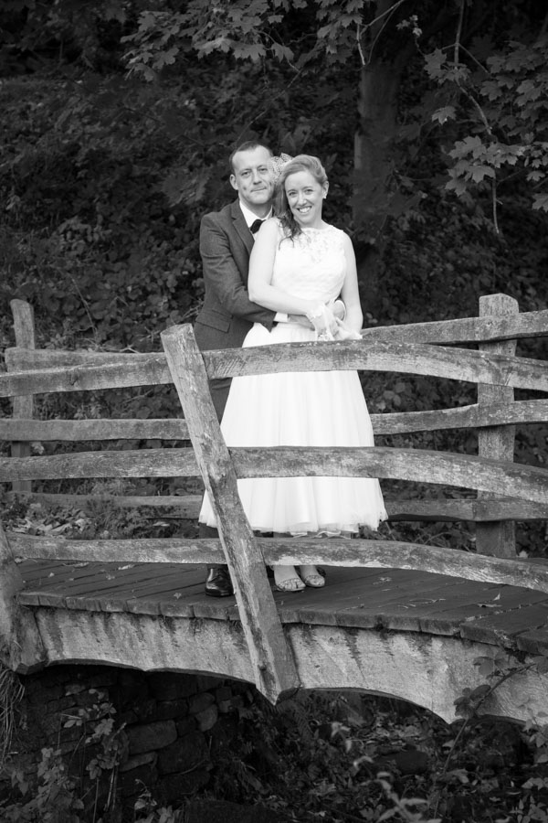 Bride and Groom cuddling on the bridge at Bradfield Village hall on their wedding day
