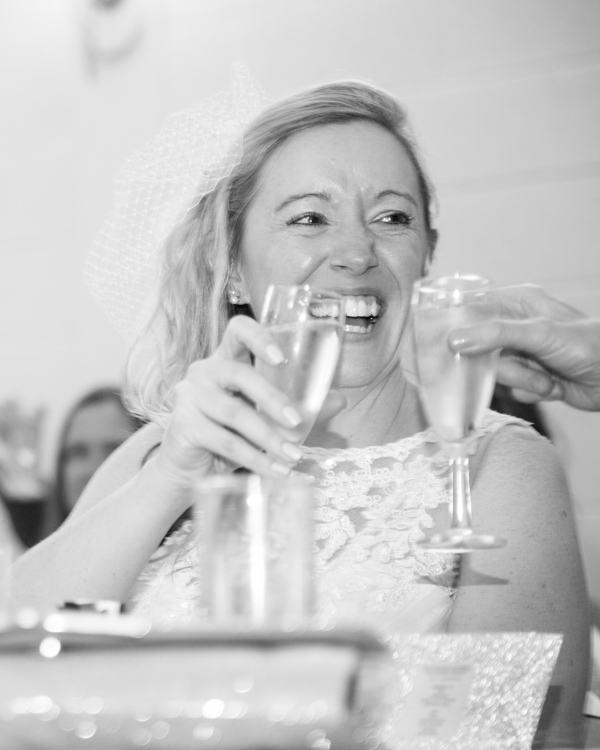 Bride laughing and drinking champagne on her wedding day