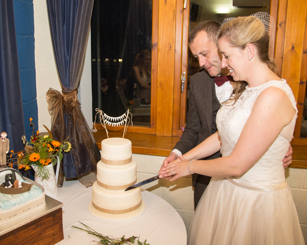Bride and Groom cutting the traditional wedding cake at Bradfield Village Hall