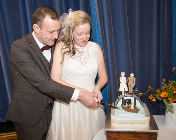 Bride and groom cutting their personalised wedding cake at Bradfield Village Hall