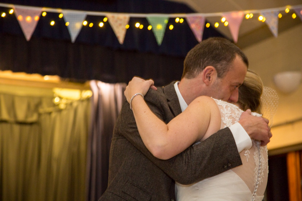 Bride and groom cuddle during their first dance
