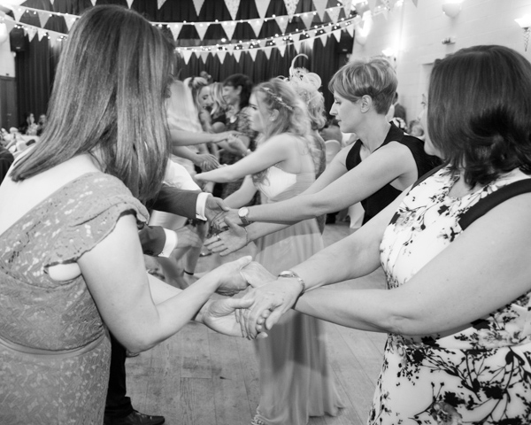 Wedding guests linking hands to dosy doe at a cailidh wedding