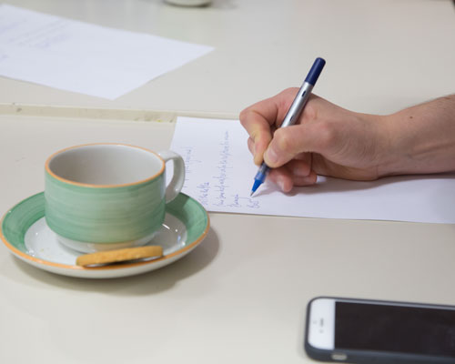 A cup of tea in a green cup and saucer on a white table next to a mobile phone and hand writing with blue pen