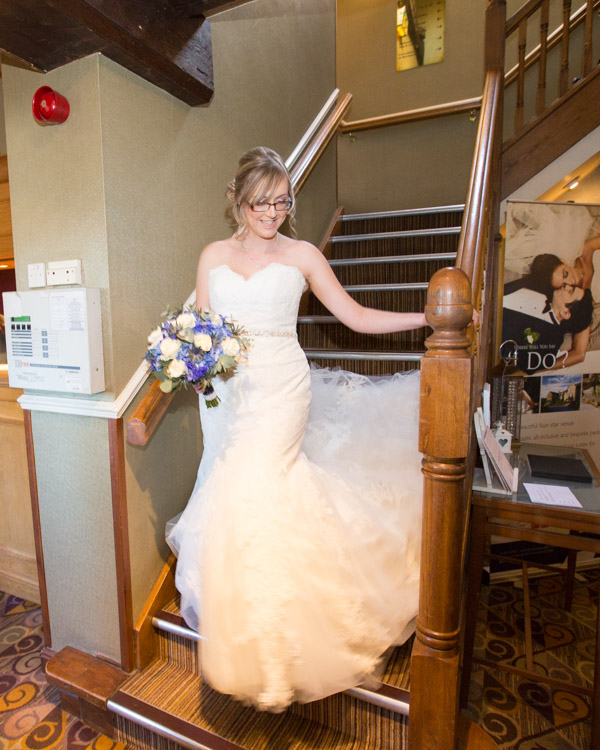 Bride walking down the staircase at Tankersley Manor Hotel