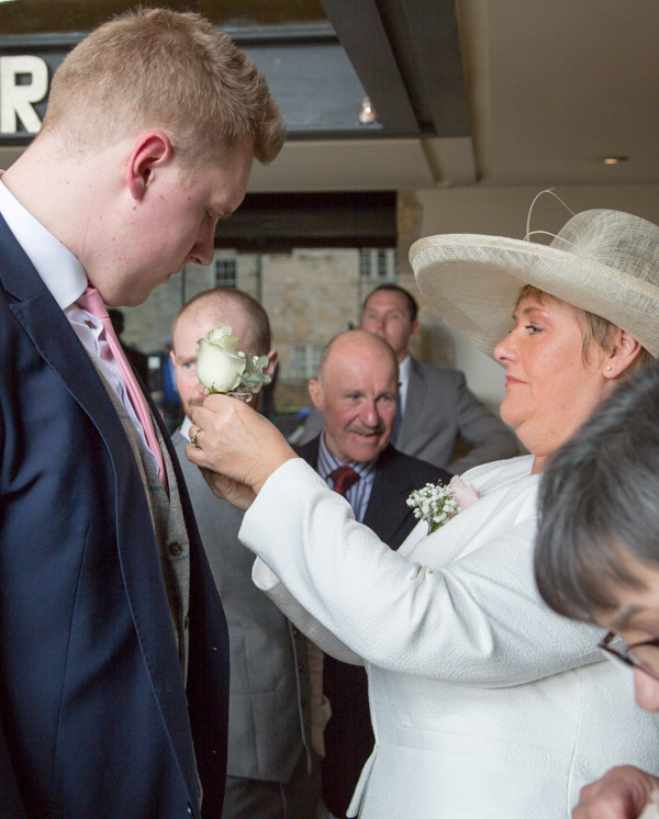 Mother of the groom fixing groomsmans buttonhole