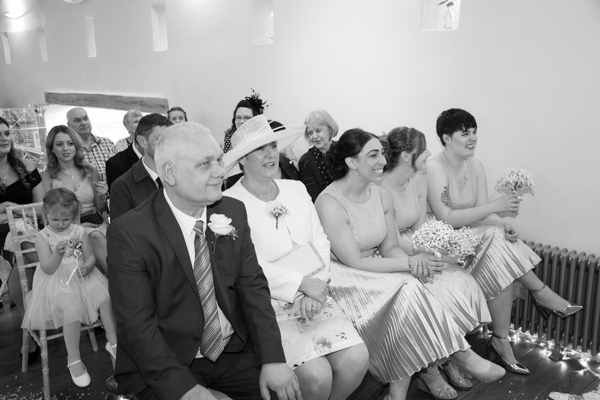 Bridesmaids and parents of the bride smiling during wedding ceremony