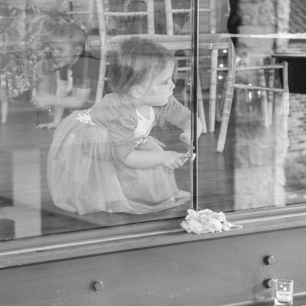 Toddler posts petals through the glass in the Priory Barn wedding
