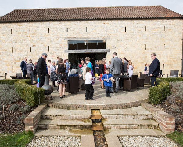 Wedding guests i the courtyard at Priory barn and cottages