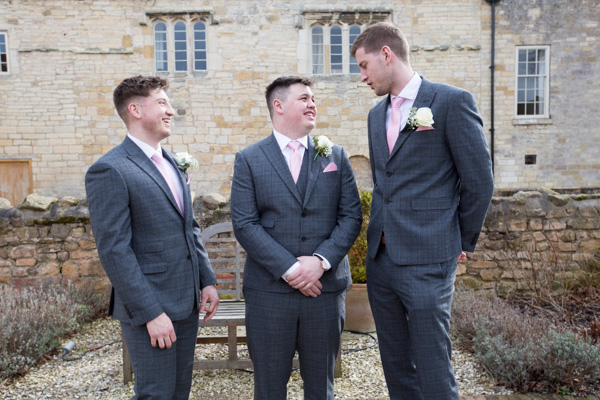 Groom and Groomsmen talking in the courtyard at Priory Barn