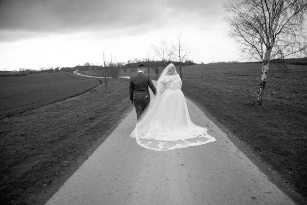 Bride and Groom walking down the path at Priory Barn an Cottages