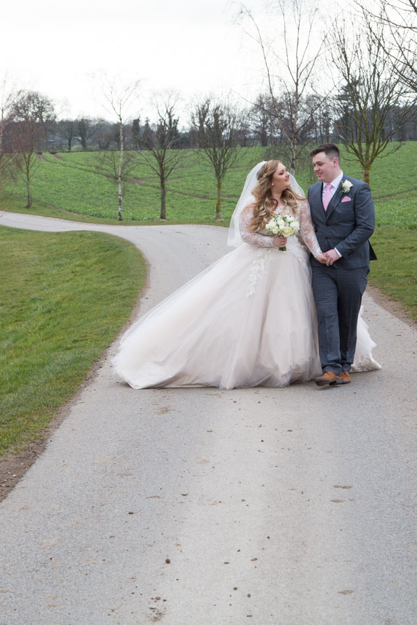 Bride and Groom walking down the path at Priory Barn and Cottages