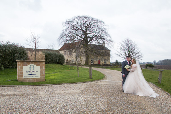 Bride and Groom kiss outside welcome sign to priory cottages and barn