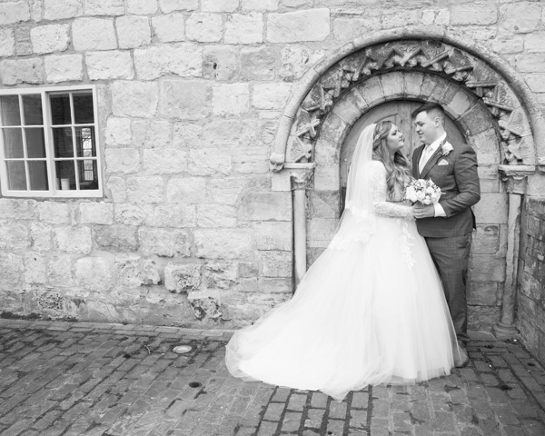 Bride and Groom standing next to stone doorway at priory barn and cottages