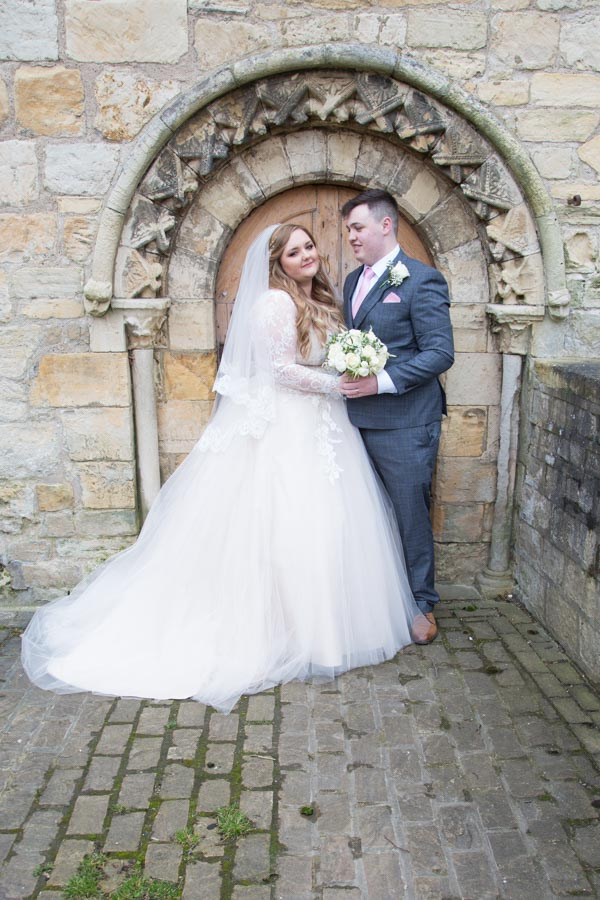 Bride and groom next to stone archway at priory barn and cottages