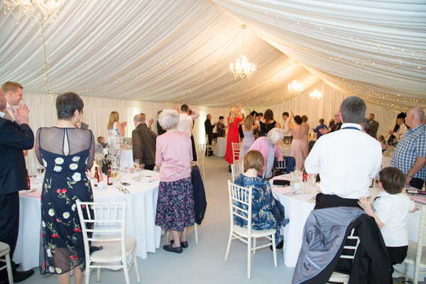 Wedding guests applauding as bride and groom enter the wedding breakfast room