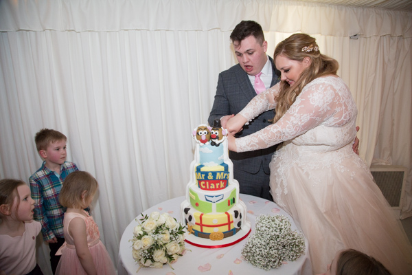 Cutting the wedding cake at Priory cottages and barn