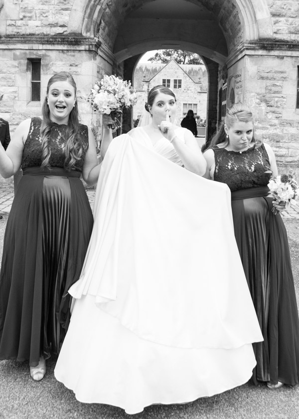 Bride and her sisters with their hands in the pockets of the wedding dress