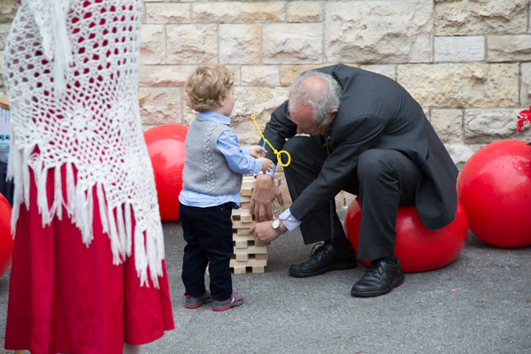 Man sitting on space hopper and playing giant jenga with young boy