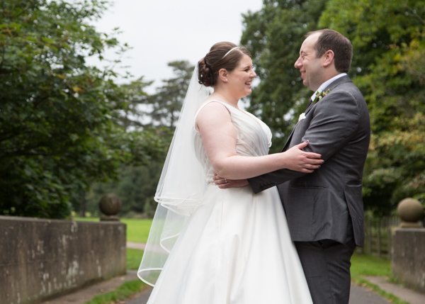 Bride and Groom holding each other and smiling in the grounds of Thoresby Hall Thoresby Courtyard Wedding